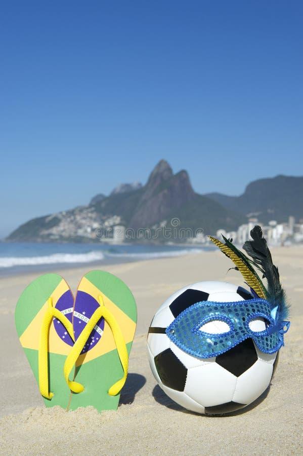 Le football et Flip Flops de ballon de football de masque de carnaval sur la plage Brésil images libres de droits