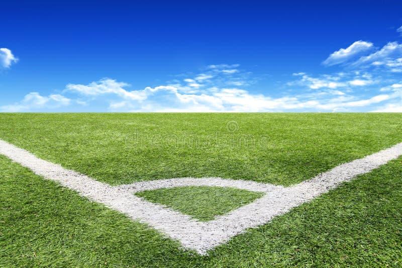 Le football et le terrain de football engazonnent le fond de ciel bleu de stade photo stock
