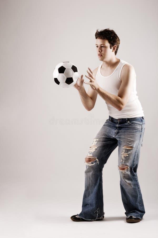 Le football jouant attrapant une bille photo libre de droits