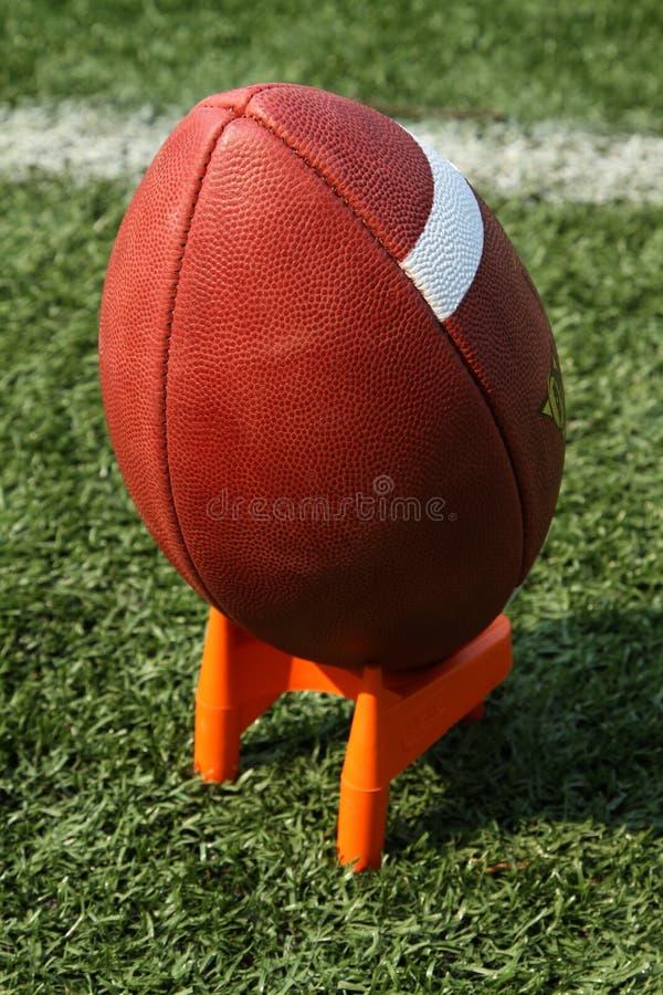Le football sur un té de coup de pied photographie stock
