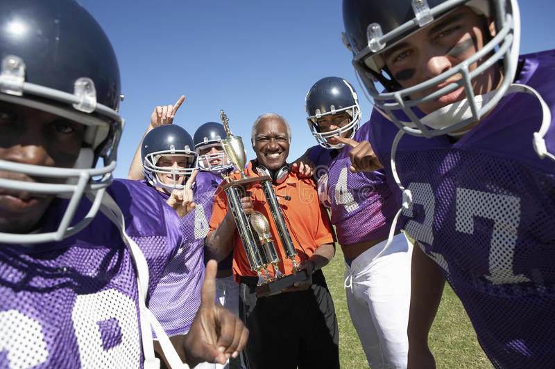 Le football Team And Coach With Trophy célébrant Victory On Field image libre de droits