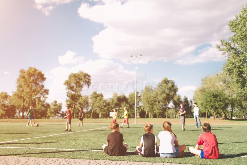Le football Team Playing Match d'enfants Partie de football pour des enfants Jeunes footballeurs s'asseyant sur le lancement Peti image stock