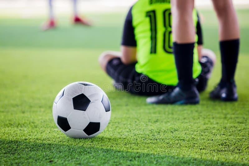 Le footballeur de femmes a mis les chaussures noires et la course de sport pour la boule de pousse au but sur le gazon artificiel photographie stock