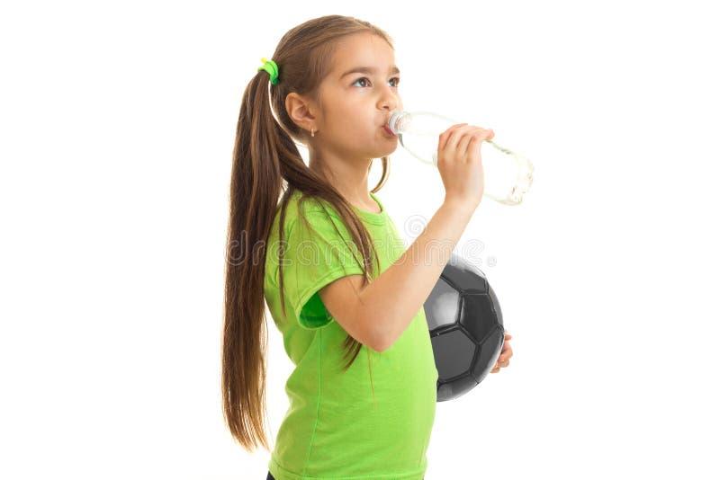 Le footballeur de petite fille boit l'eau d'une bouteille photographie stock libre de droits