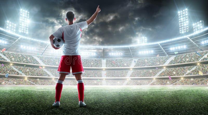 Le footballeur tient un ballon de football sur le stade professionnel et parler aux fans Vue par derrière images stock