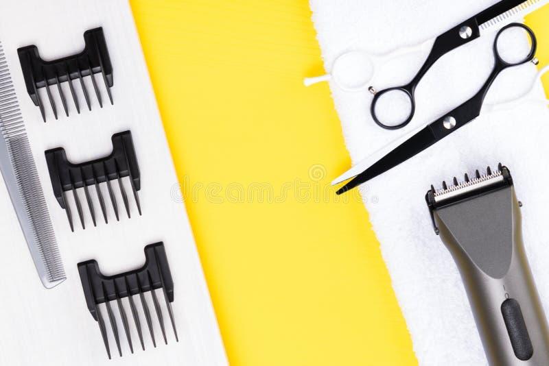 Le forbici e lo stilista hanno messo su un fondo giallo della tavola fotografie stock