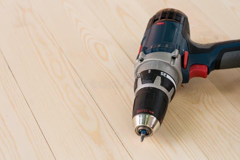 Le foret sans fil d'accu au-dessus des planches de conseils en bois ajournent le fond images stock