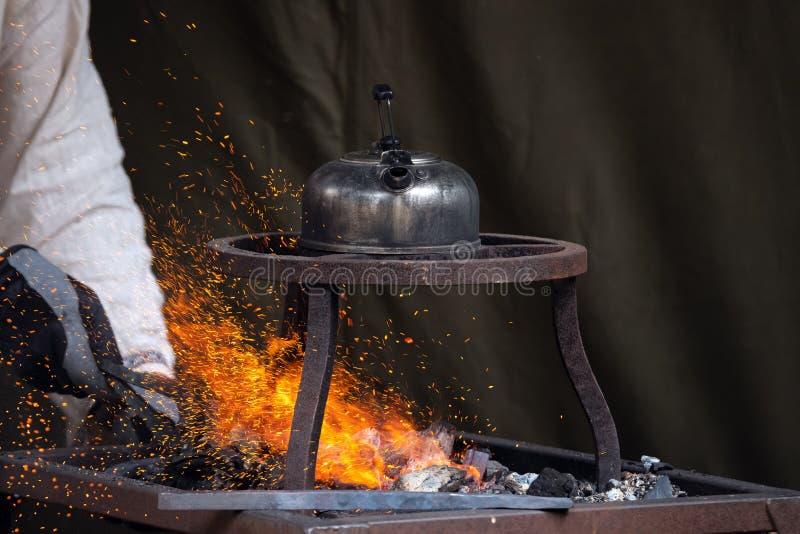 Le forgeron chauffe le métal dans du charbon rouge chaud tandis que le théier fait bouillir l'eau sur le dessus L'artisan forge à photos libres de droits