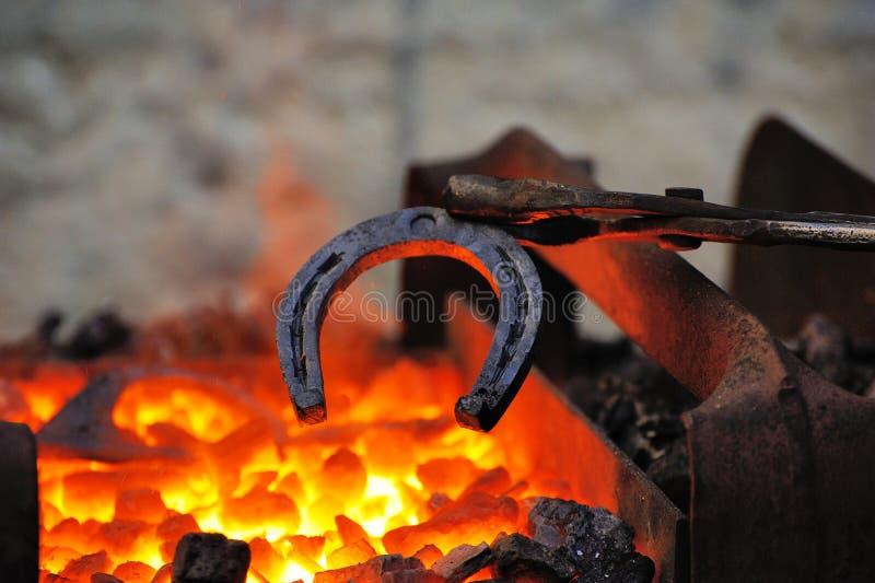 Le forgeron forge un fer à cheval photographie stock libre de droits
