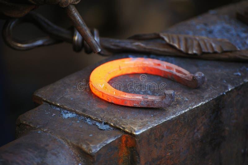 Le forgeron forge un fer à cheval images libres de droits