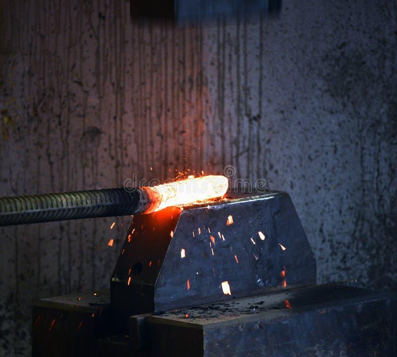 Le forgeron forge un fer d'un rouge ardent image stock