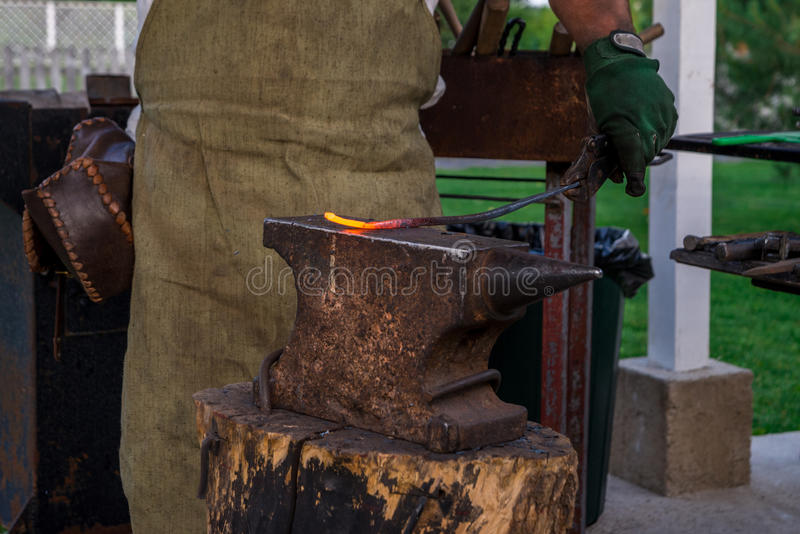 Le forgeron juge une barre en métal passionnée à la fonte sur l'enclume, befo image libre de droits