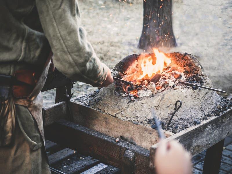 Le forgeron tient la billette au-dessus des charbons chauds dans un four d'argile fabrication de chauffage d'épée en métal de fer images libres de droits