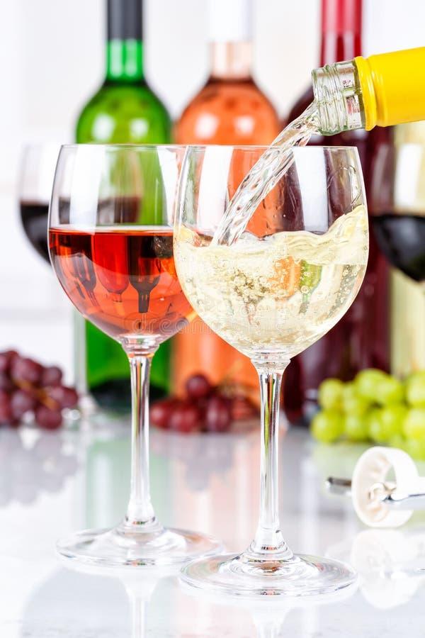 Le format de portrait blanc de versement de bouteille en verre de vin versent photo libre de droits