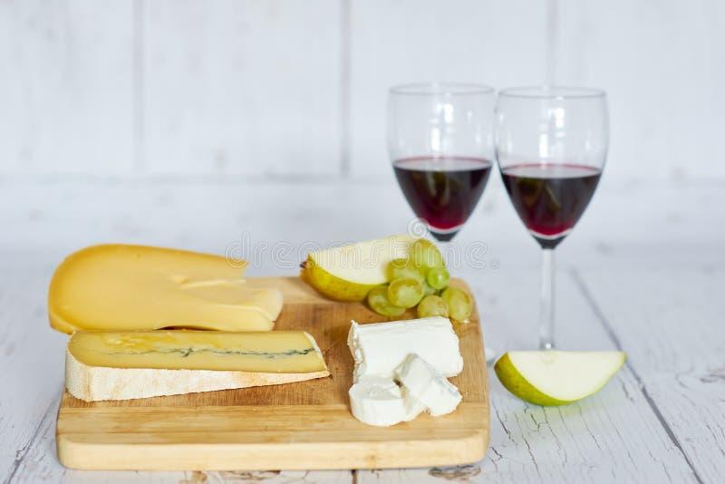 Le foto due vetri di vino rosso, della pera e del formaggio imbarcano sul vassoio di legno fotografia stock libera da diritti