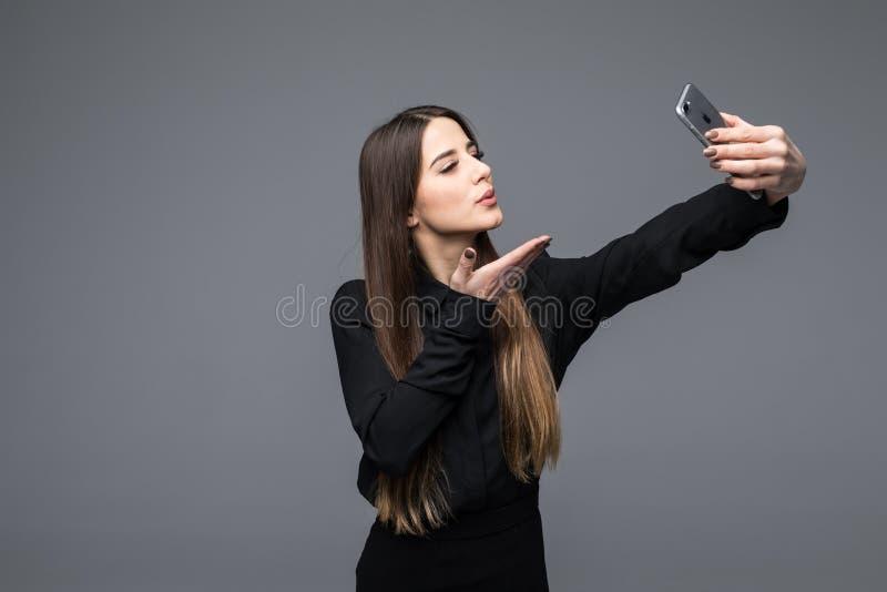 Le fotoet för affärskvinnadanandeselfie på smartphonen Stå över grå bakgrund arkivbilder