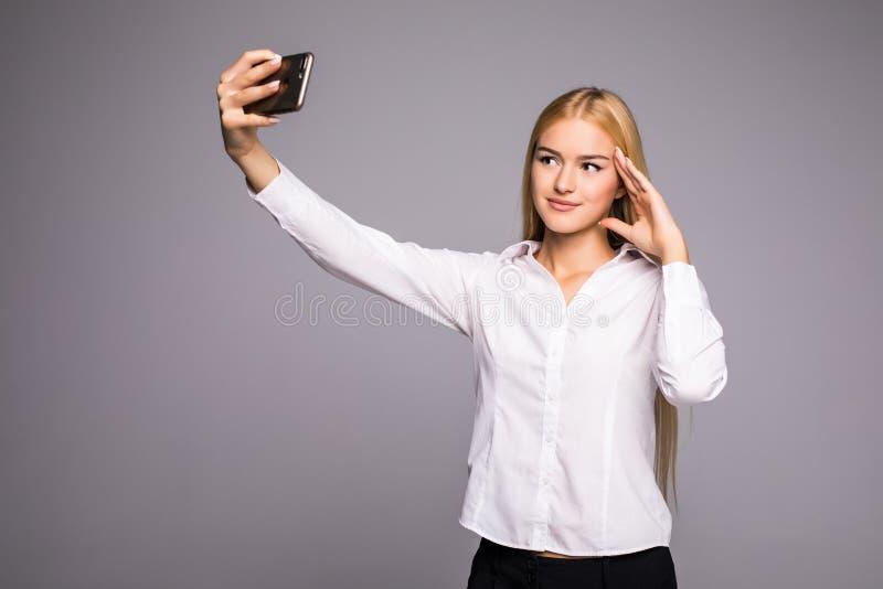 Le fotoet för affärskvinnadanandeselfie på smartphonen Stå över grå bakgrund royaltyfria foton