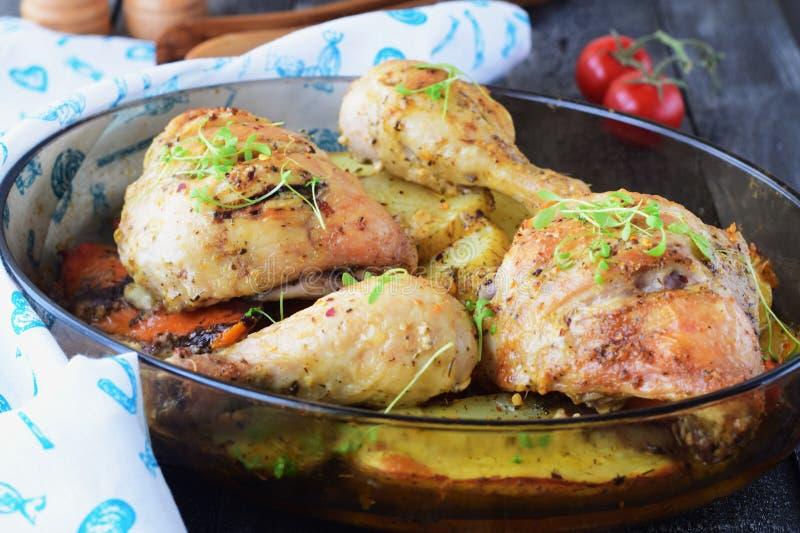 Le four a fait cuire le poulet avec la pomme de terre et la patate douce, les épices, herbes en huile d'olive Cuisine familiale,  photos libres de droits