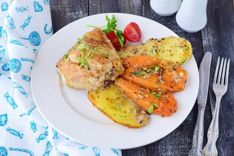 Le four a fait cuire le poulet avec la pomme de terre et la patate douce, les épices, herbes en huile d'olive Cuisine familiale,  images libres de droits