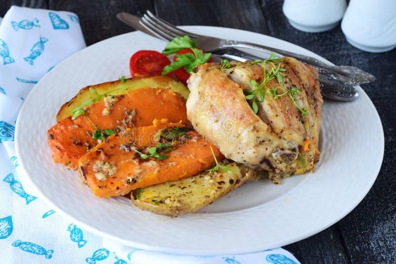 Le four a fait cuire le poulet avec la pomme de terre et la patate douce, les épices, herbes en huile d'olive Cuisine familiale,  image libre de droits