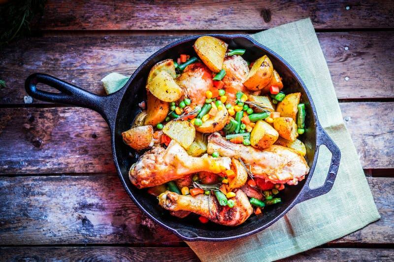 Le four a fait le poulet cuire au four avec des pommes de terre et des légumes sur le backgr en bois image libre de droits