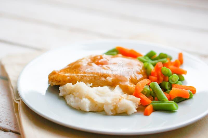Le four a fait le poulet cuire au four en sauce au jus avec de la purée de pommes de terre et les légumes photographie stock