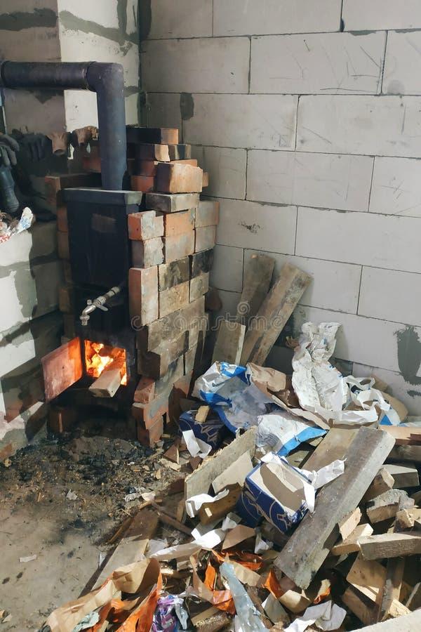 Le fourneau à bois brûle avec des portes ouvertes en violation de la sécurité et constitue une menace pour le bâtiment par l photographie stock libre de droits