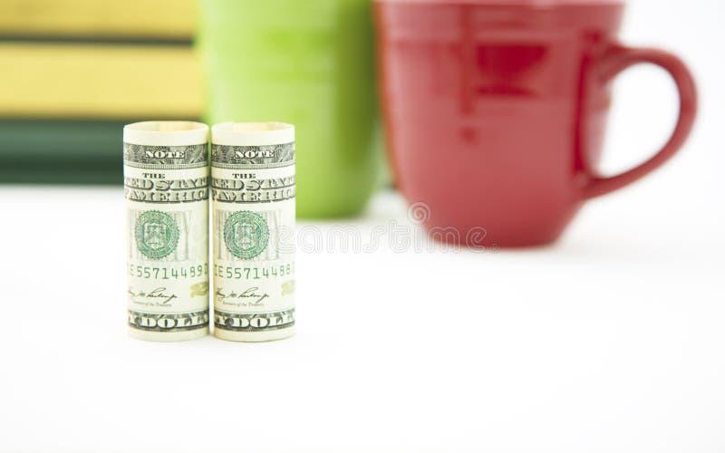 Le foyer financier monétaire avec des livres et les tasses soutiennent dedans image stock