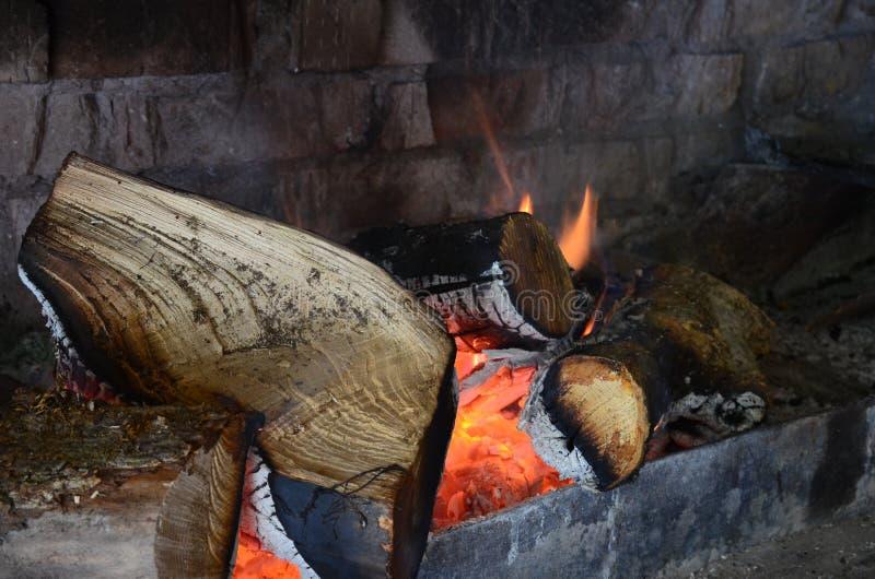 Le foyer par la brique avec brûler les rondins en bois photo libre de droits