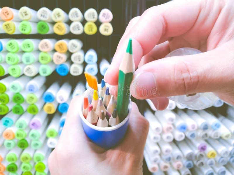 Le foyer sur la main de femmes sélectionnent le stylo de couleur sur la boîte avec le fond d'étagère de stylo de couleur photo stock