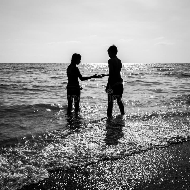 Le frère et la soeur à la soirée en mer ondule photo stock