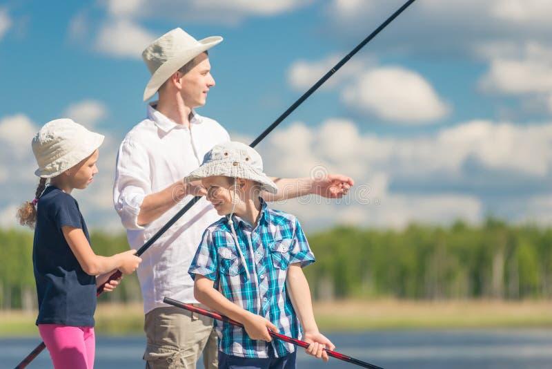 Le frère et la soeur avec le père sur la pêche avec pêcher r photographie stock libre de droits