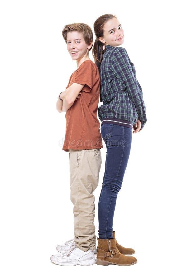 Le frère et la soeur de sourire comparent leur taille photo stock