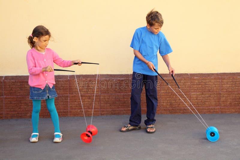 Le frère et la soeur jouent avec le jouet de yo-yo images libres de droits