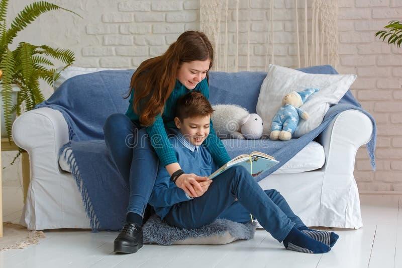 Le frère et la soeur lisent un livre photo libre de droits