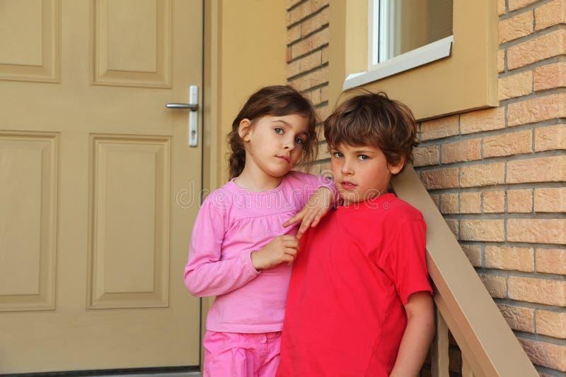 Le frère et la soeur restent la trappe proche de la maison photographie stock