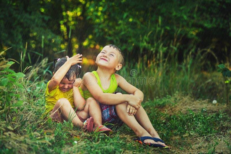 Le frère et la soeur s'asseyant sur l'herbe sous l'été pleuvoir photographie stock libre de droits