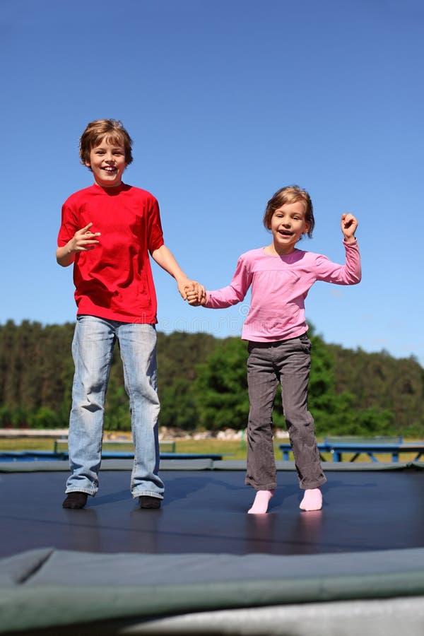 Le frère et la soeur sautent sur le tremplin photographie stock libre de droits