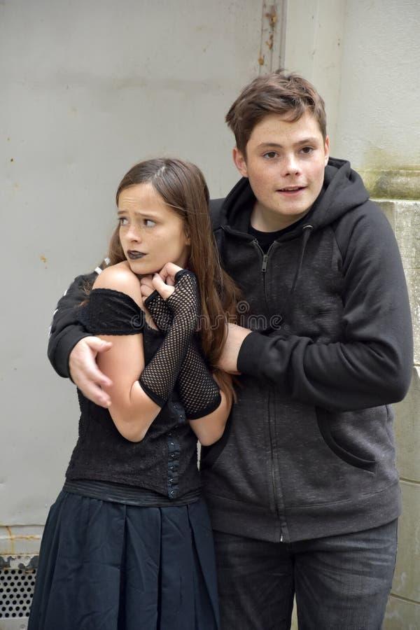 Le frère mignon d'adolescent protège sa petite soeur effrayée image stock