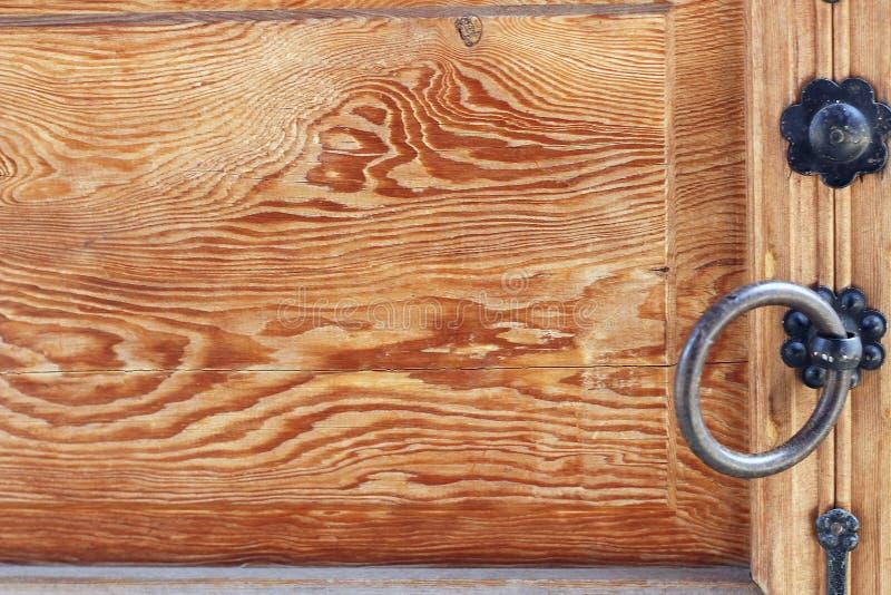 Le fragment de la porte en bois antique avec du fer manipule étroit  photographie stock