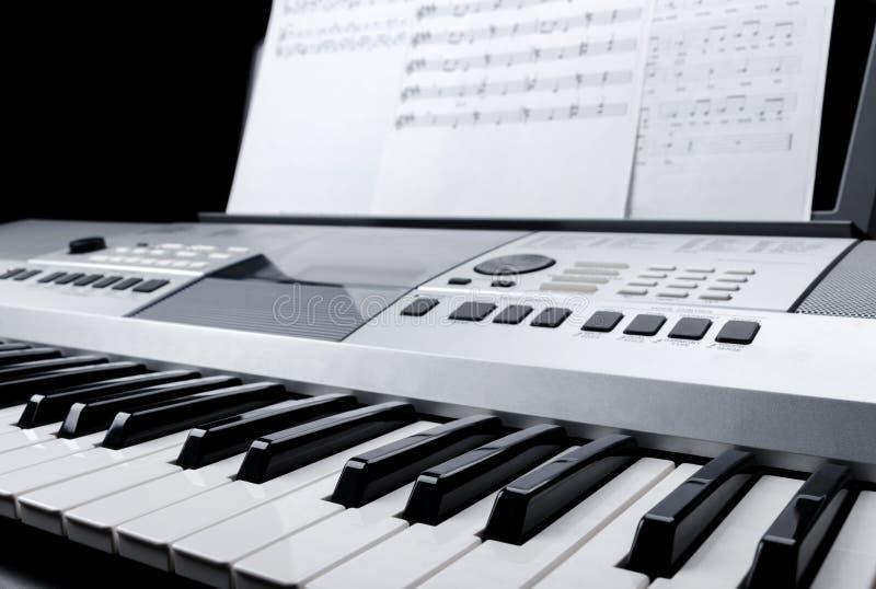 Le fragment du clavier électronique de synthétiseur avec des boutons et la musique de contrôle note des feuilles photos libres de droits