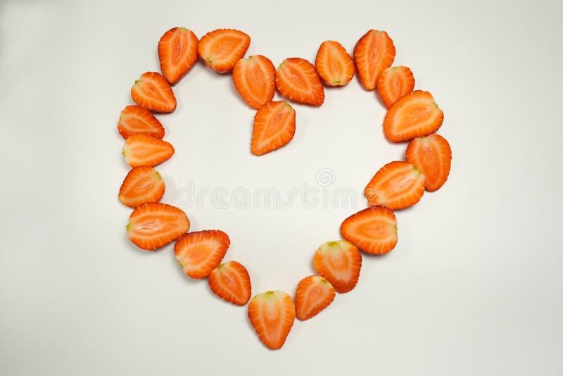le fragole mature incidono le metà su un fondo bianco, hanno presentato un grande cuore immagine stock