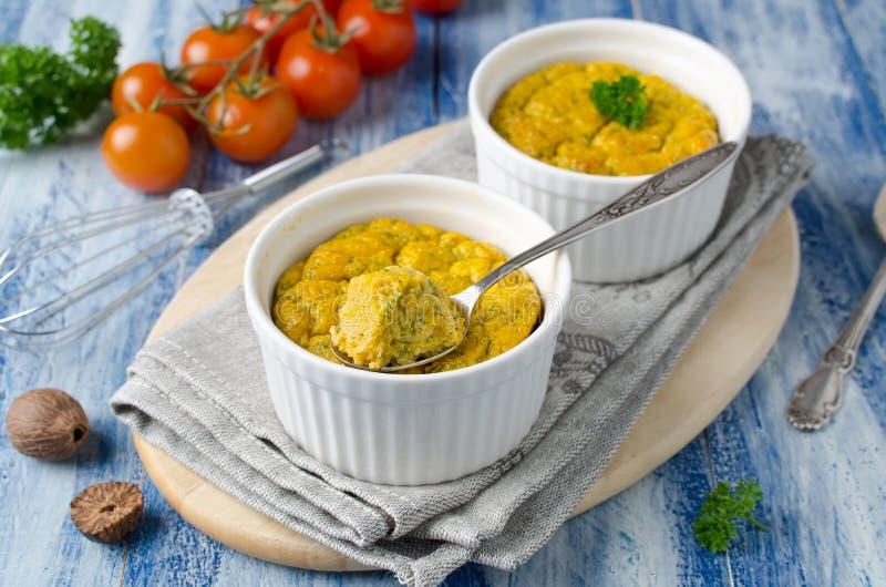 Le Français a fait le soufflé cuire au four de fromage avec les carottes et l'aneth dans le ramek blanc photos libres de droits
