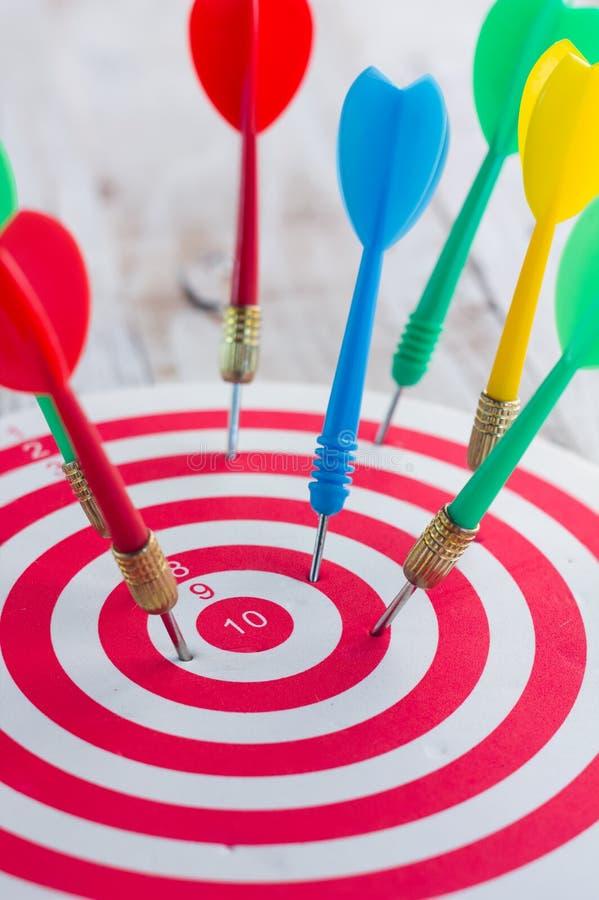 Le frecce dardeggiano colpire il centro di un obiettivo immagini stock libere da diritti