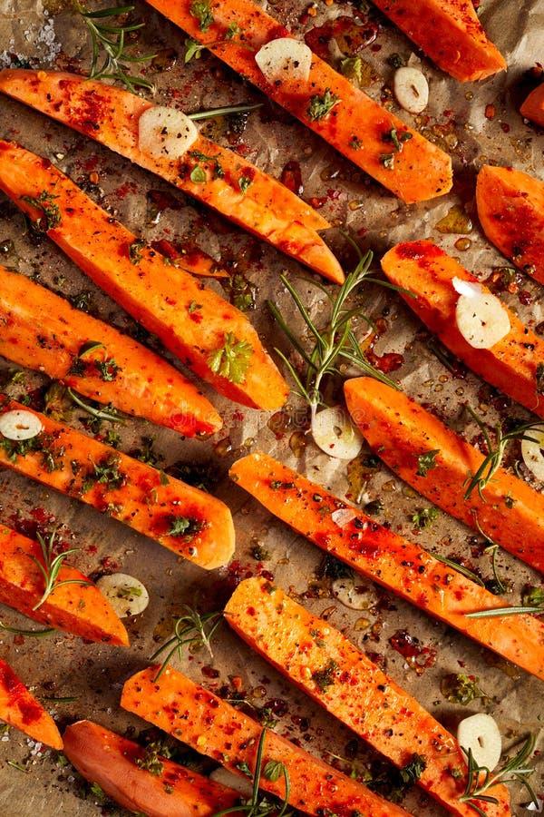 Le fritture crude dalle patate dolci esperte con le erbe, l'aglio, il sale marino e l'olio d'oliva hanno preparato per cuocere su fotografie stock libere da diritti