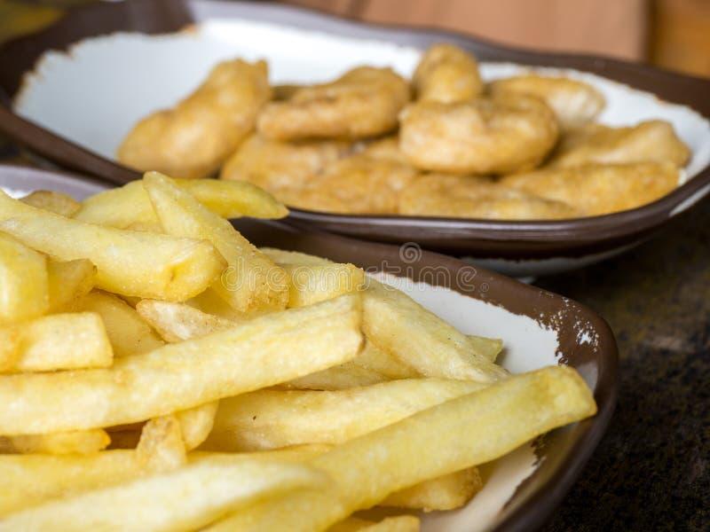 Le fritture di Fried French e le pepite di pollo su un piatto bianco con marrone rasentano la tavola di legno fotografia stock libera da diritti