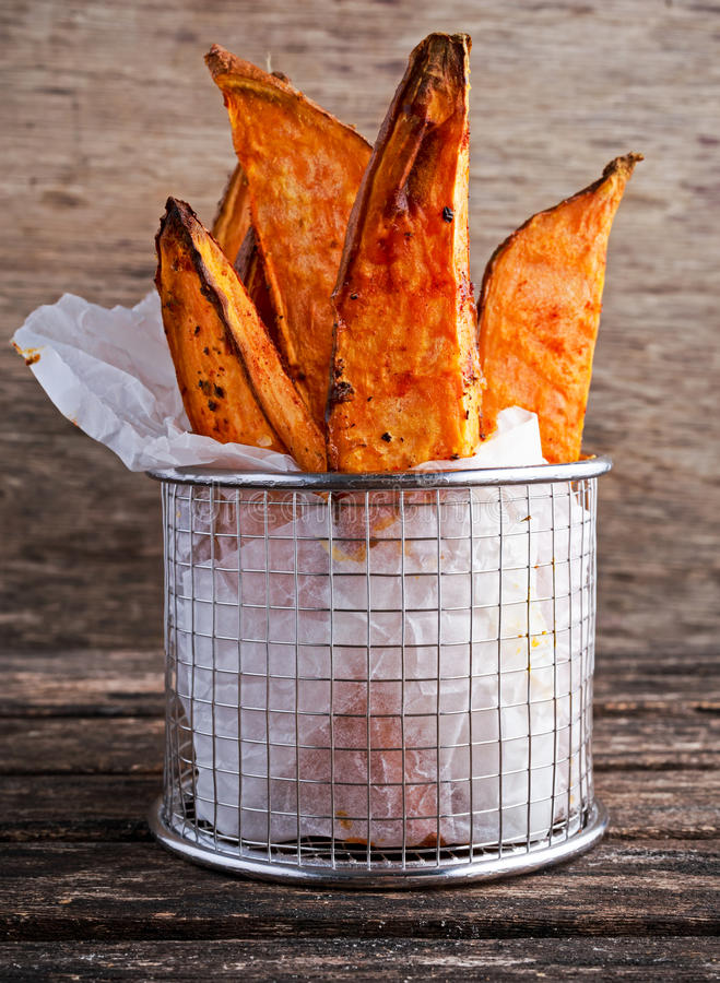 Le fritture organiche dolci di recente cucinate della patata in involucro di carta eseguito in un servizio metal il canestro sull fotografia stock libera da diritti