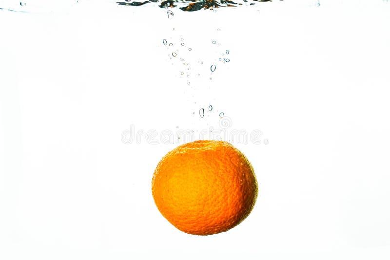 Le friut frais tombe dans l'eau avec l'éclaboussure et les bulles photo stock