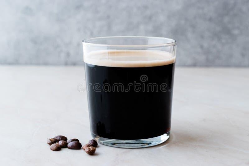 Le froid écumeux préparent le café nitro avec des haricots prêts à boire photo libre de droits
