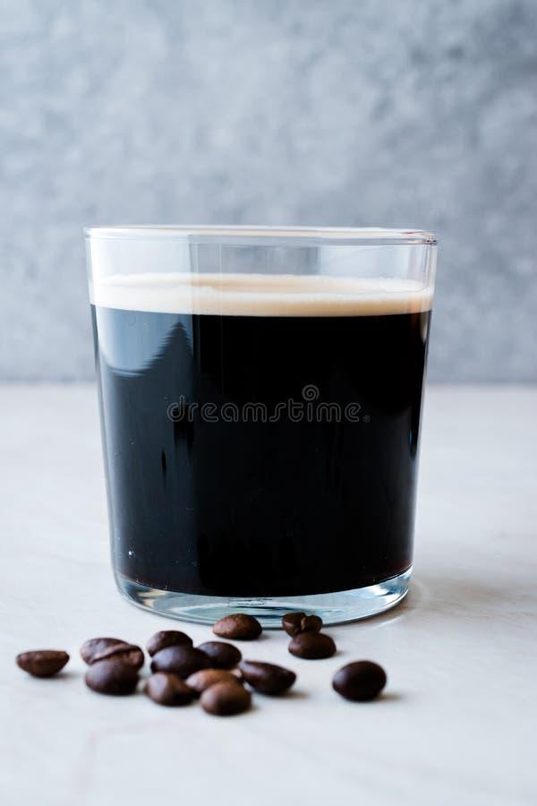Le froid écumeux préparent le café nitro avec des haricots prêts à boire photos libres de droits